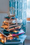 image shows pile of books underneath a lantern, with little lights trickling down